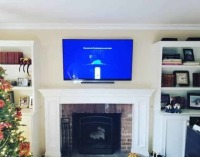 4k OLED TV installed over a fireplace